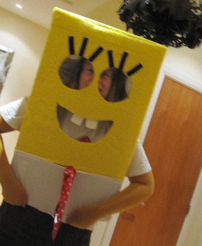 SpongeBob costume made with a cardboard box, yellow flannel, white t-shirt and brown shorts