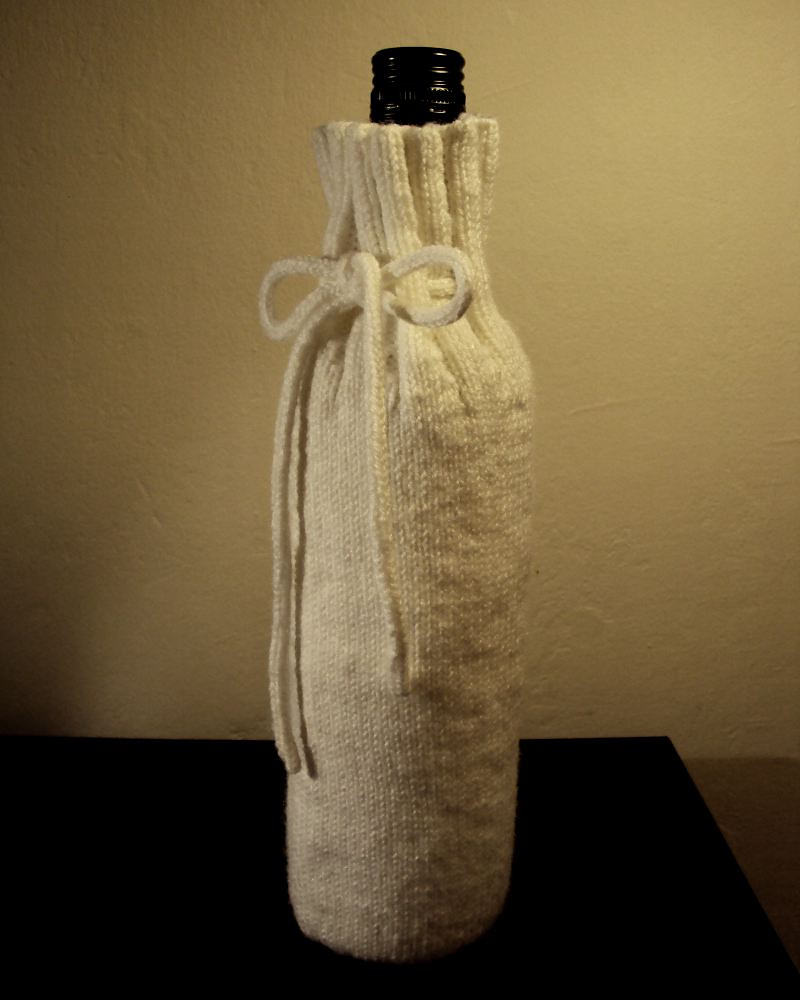 knitted wine bottle cosy in white yarn