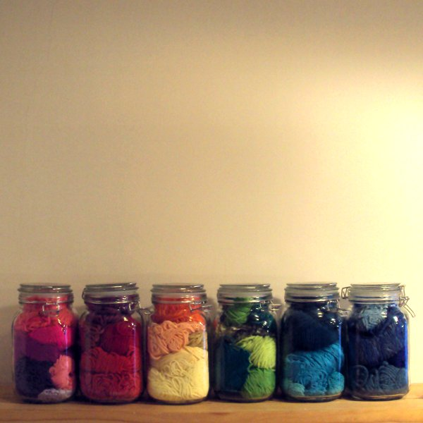 Six jars full of coloured yarn, pink, red, yellow, green, teal and blue