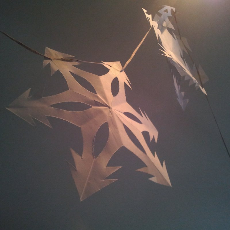 Six-sided paper snowflakes strung up as a Christmas decoration